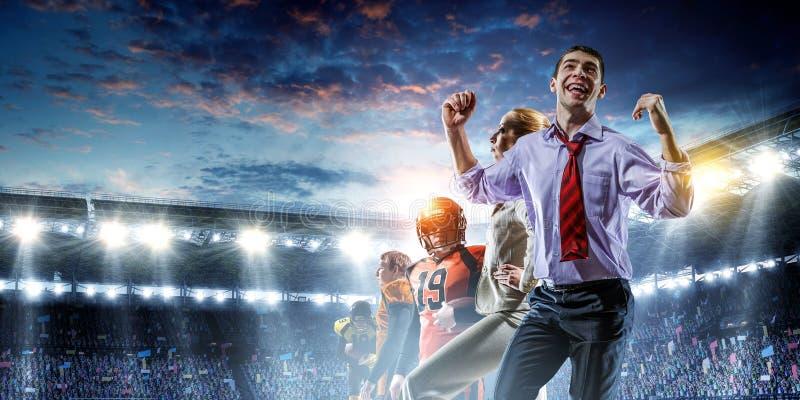 Gruppo di affari su stadio di football americano Media misti immagine stock libera da diritti