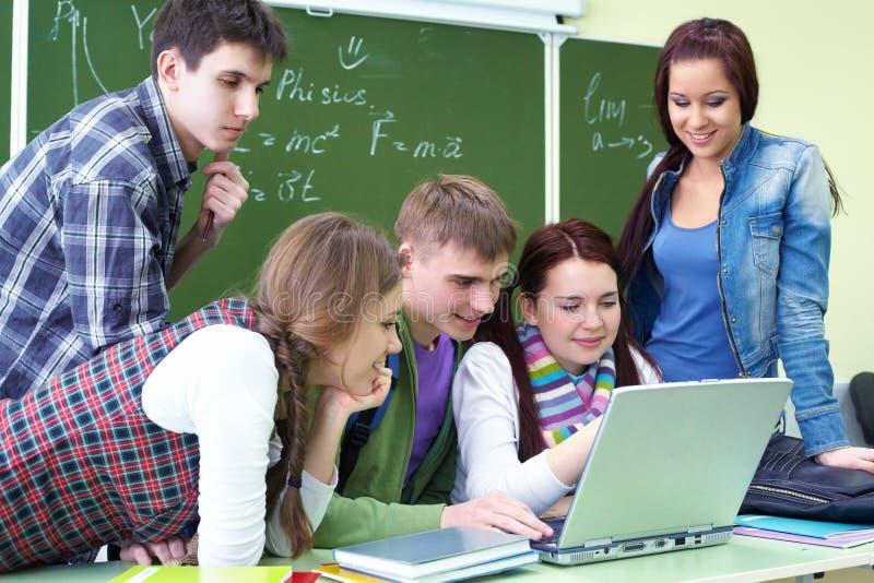 Gruppo di allievi che studiano con il computer portatile fotografie stock