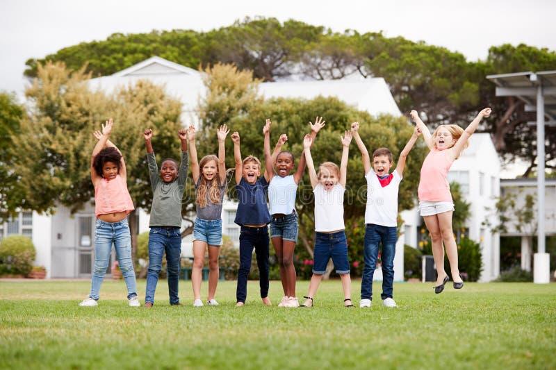 Gruppo di allievi emozionanti della scuola elementare che stanno sul campo da gioco al tempo della rottura con le armi alzate fotografia stock