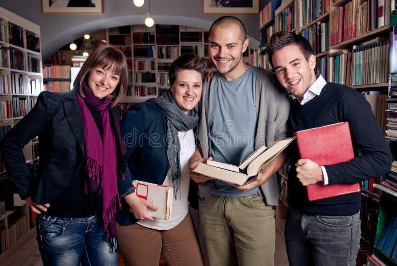 Gruppo di allievi felici ad una libreria fotografie stock libere da diritti