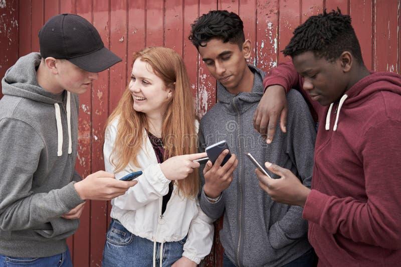 Gruppo di amici adolescenti che esaminano i telefoni cellulari nell'ambiente urbano fotografia stock