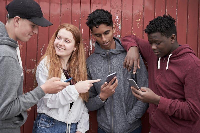 Gruppo di amici adolescenti che esaminano i telefoni cellulari nell'ambiente urbano fotografie stock libere da diritti