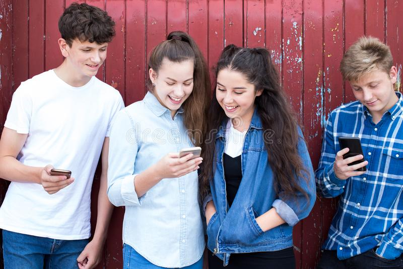 Gruppo di amici adolescenti che esaminano i telefoni cellulari in Setti urbano fotografia stock