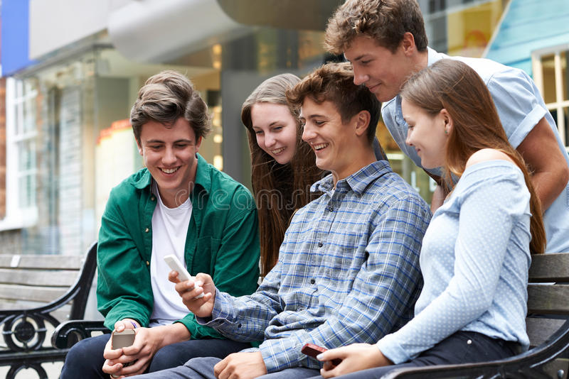 Gruppo di amici adolescenti che leggono messaggio di testo in città fotografia stock libera da diritti