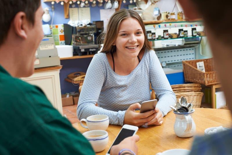 Gruppo di amici adolescenti che si incontrano in caffè e che per mezzo dei telefoni cellulari fotografia stock libera da diritti
