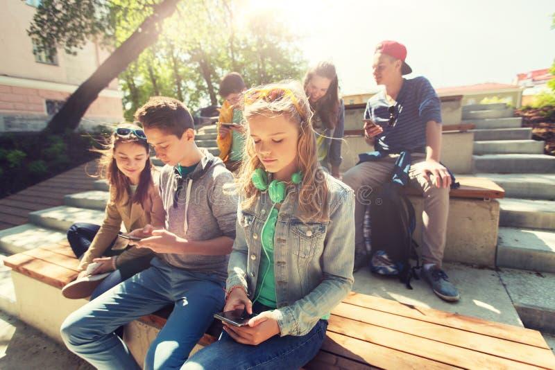 Gruppo di amici adolescenti con gli smartphones all'aperto fotografia stock libera da diritti
