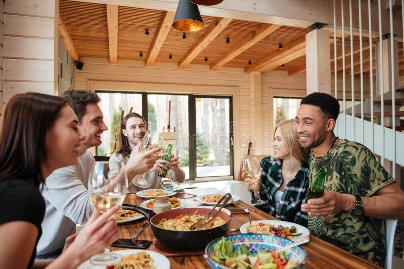 Gruppo di amici cenando e ridendo della tavola fotografia stock