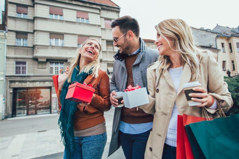 Gruppo di amici che camminano lungo la via con i sacchetti della spesa fotografia stock libera da diritti