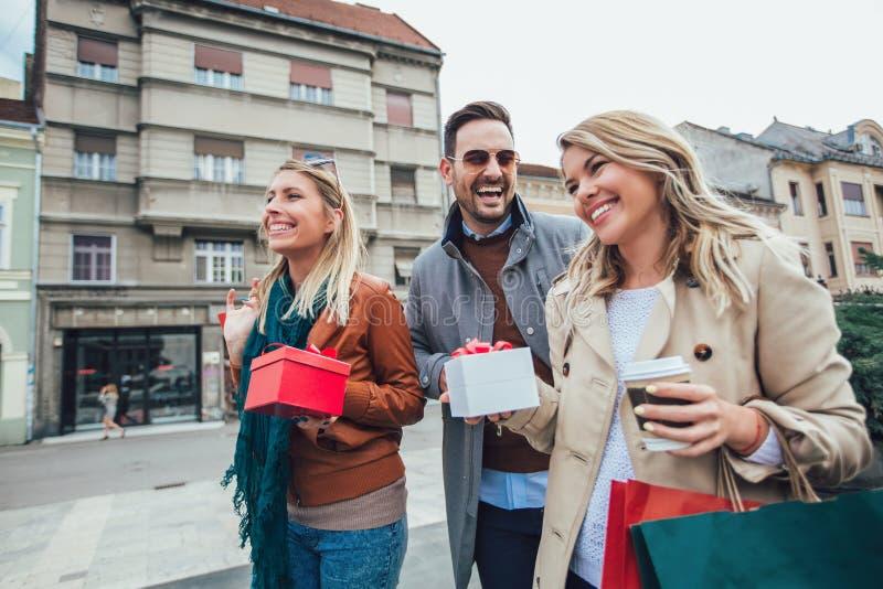 Gruppo di amici che camminano lungo la via con i sacchetti della spesa fotografia stock