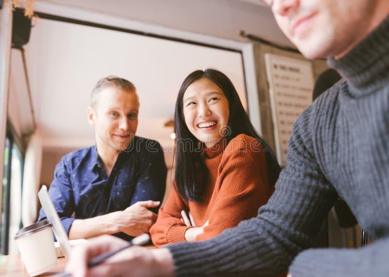 Gruppo di amici che chiacchierano e che utilizzano computer portatile nel caffè al caffè della caffetteria in università che parl fotografia stock