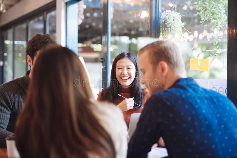 Gruppo di amici che chiacchierano e che utilizzano computer portatile nel caffè al caffè della caffetteria in università che parl fotografie stock