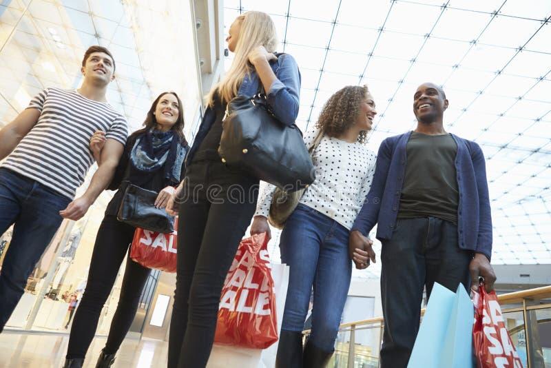 Gruppo di amici che comperano insieme nel centro commerciale immagine stock