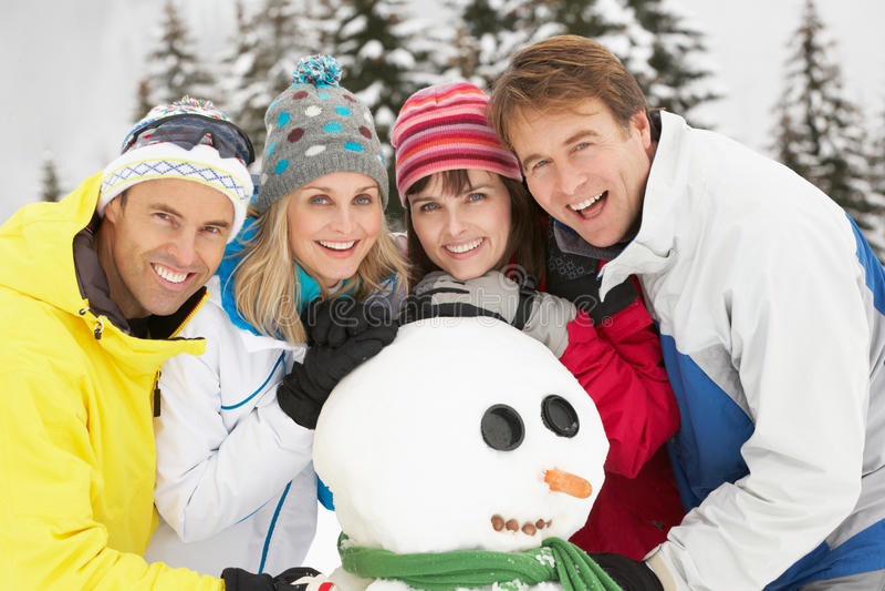 Gruppo di amici che costruiscono pupazzo di neve sulla festa del pattino fotografie stock