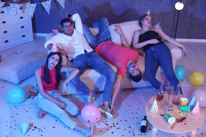 Gruppo di amici che dormono nella stanza sudicia dopo il partito fotografie stock libere da diritti