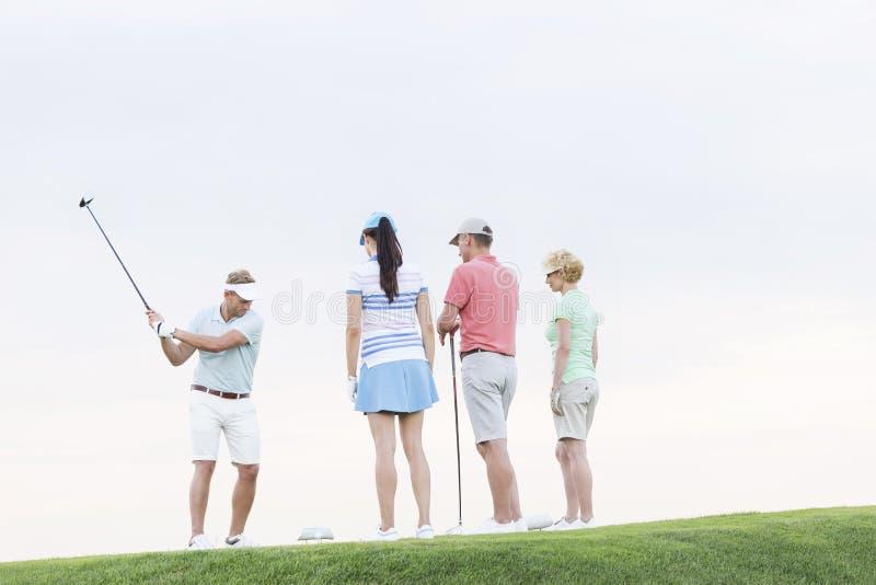 Gruppo di amici che esaminano uomo che gioca golf contro il chiaro cielo fotografia stock