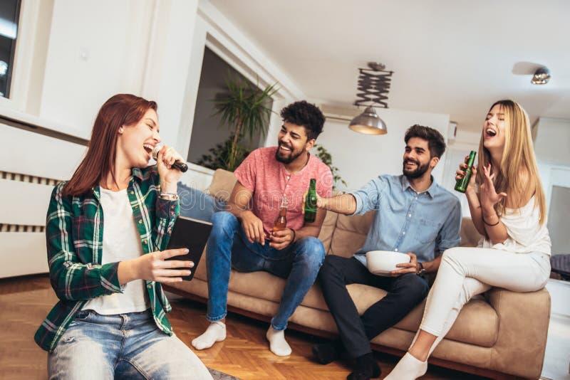 Gruppo di amici che giocano karaoke a casa immagini stock