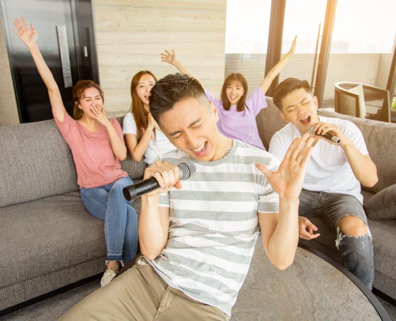 Gruppo di amici che giocano karaoke a casa fotografia stock libera da diritti