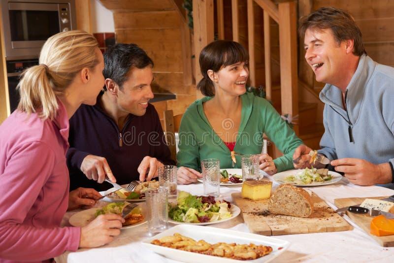 Gruppo di amici che godono del pasto in chalet alpino immagini stock