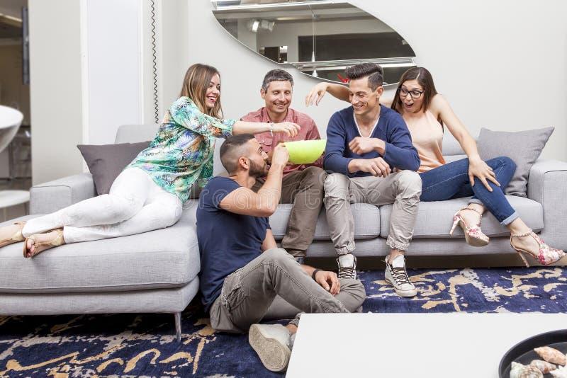 Gruppo di amici che guardano TV e che mangiano popcorn sul sofà fotografia stock libera da diritti