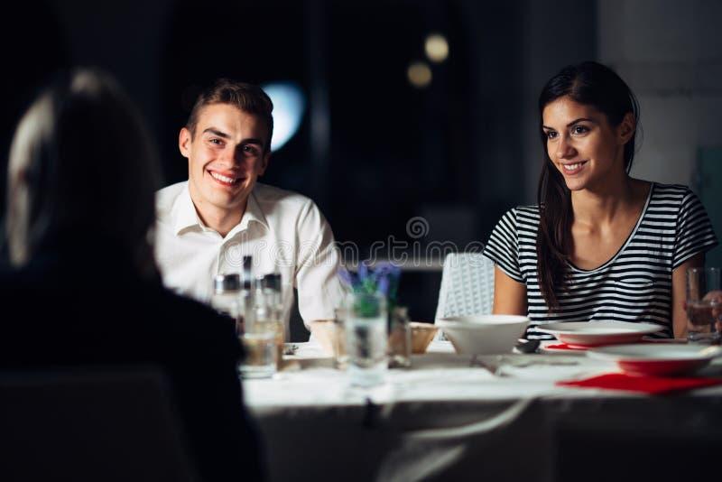 Gruppo di amici che hanno una cena in un ristorante Appuntamento a quattro Notte attraente della gente fuori, pranzando in un hot fotografia stock