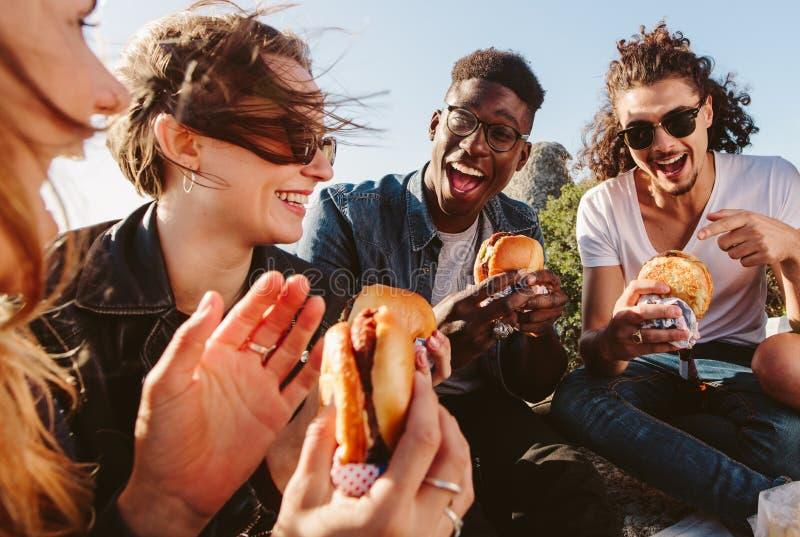 Gruppo di amici che mangiano hamburger sulla cima della montagna fotografia stock