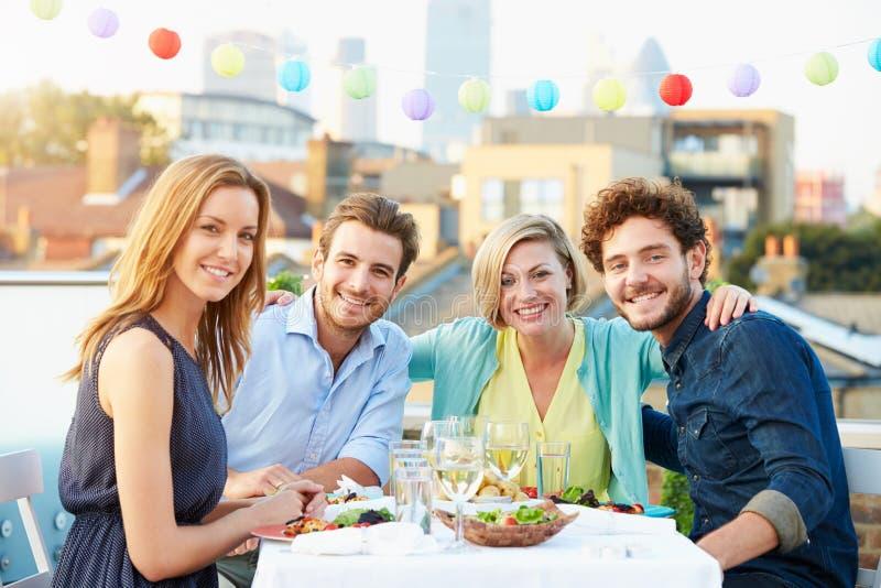 Gruppo di amici che mangiano pasto sul terrazzo del tetto fotografie stock