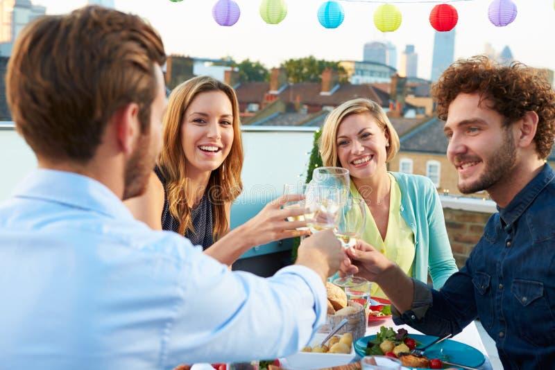 Gruppo di amici che mangiano pasto sul terrazzo del tetto immagini stock