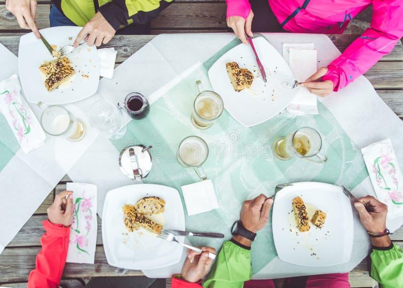 Gruppo di amici che mangiano strudel e che bevono birra in un ristorante sulle montagne fotografie stock