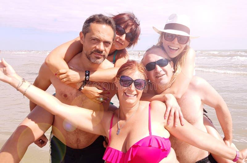 Gruppo di amici che prendono divertimento sulla spiaggia fotografia stock