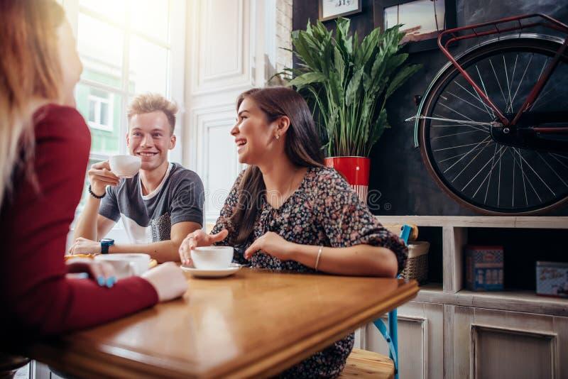 Gruppo di amici che si incontrano al caffè e caffè o tè bevente, chiacchierare e ridere immagine stock