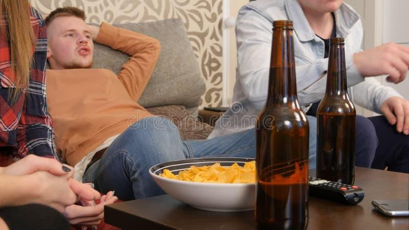 Gruppo di amici che si siedono insieme sul sofà, sulla TV di sorveglianza e sulla birra bevente fotografie stock libere da diritti