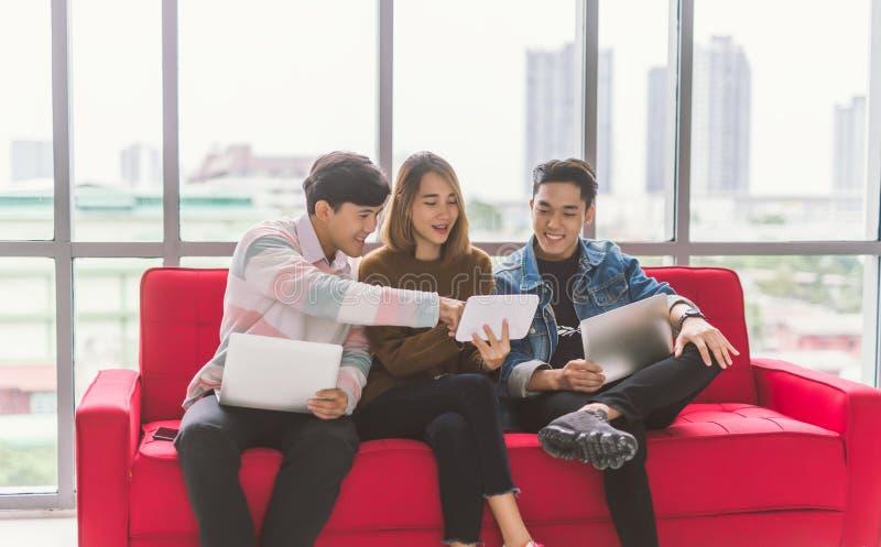 Gruppo di amici che si siedono sul sofà facendo uso della tecnologia dello smartphone e del computer portatile fotografie stock