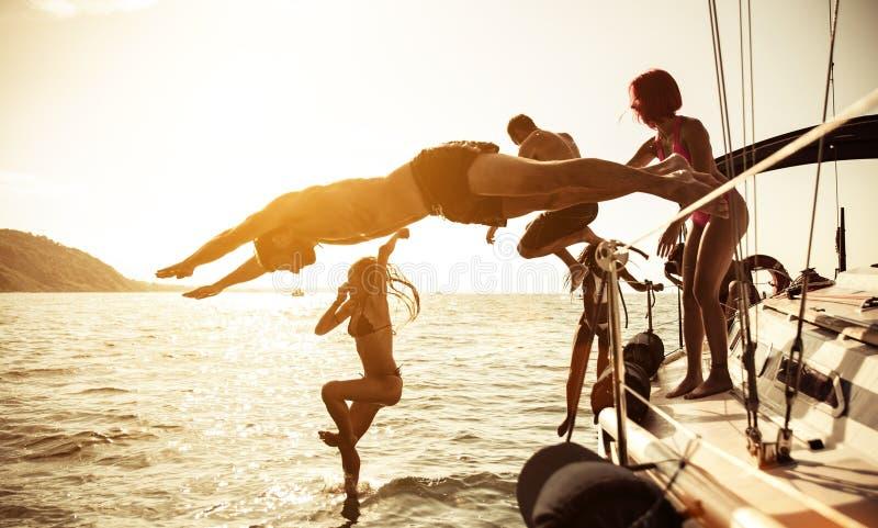 Gruppo di amici che si tuffano l'acqua durante l'escursione della barca immagine stock libera da diritti