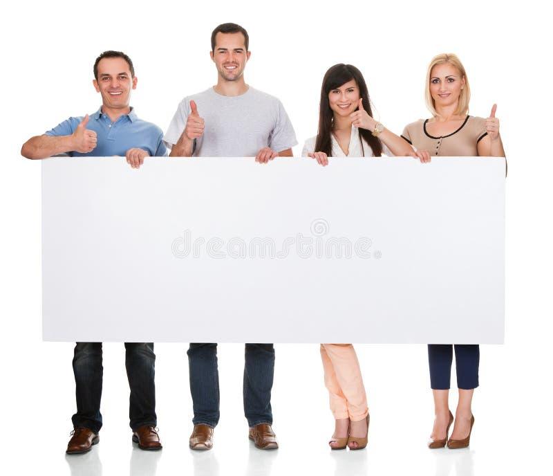 Gruppo di amici che tengono cartello fotografia stock libera da diritti