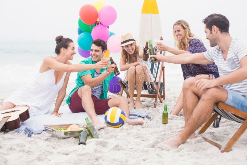 Gruppo di amici che tostano le bottiglie di birra sulla spiaggia fotografia stock libera da diritti