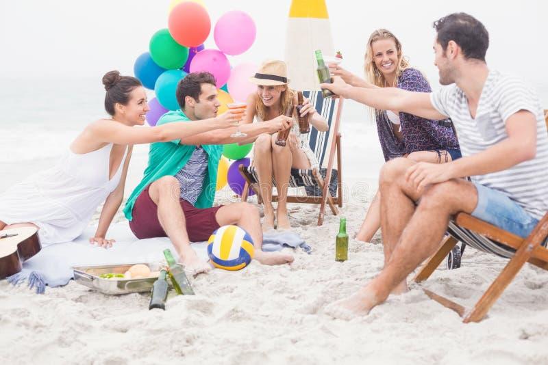 Gruppo di amici che tostano le bottiglie di birra sulla spiaggia fotografia stock