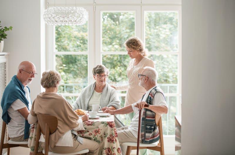 Gruppo di amici con il personale sanitario utile che si siede insieme alla tavola alla sala da pranzo di casa di cura fotografia stock