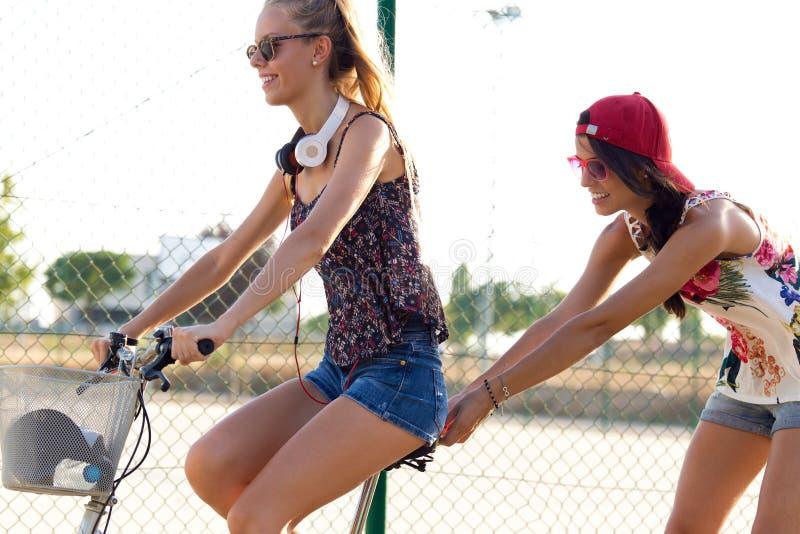 Gruppo di amici con la guida dei pattini e della bici di rullo nel parco fotografia stock