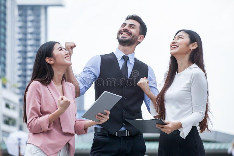 gruppo di amici delle donne e del giovane che per mezzo di una compressa e ridendo all'aperto tre persone dell'affare emozionante immagine stock libera da diritti