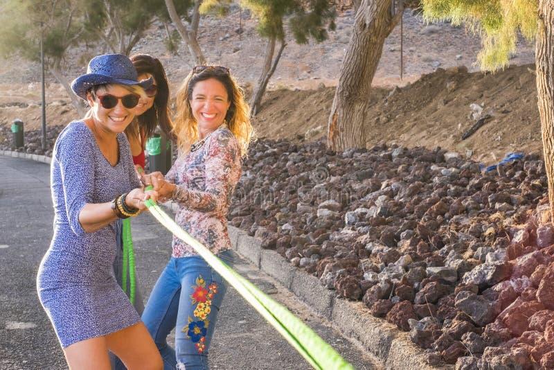 Gruppo di amici delle femmine con stile casuale dei vestiti colorati e felici per godere di insieme di giocare con un cavo svago  fotografia stock