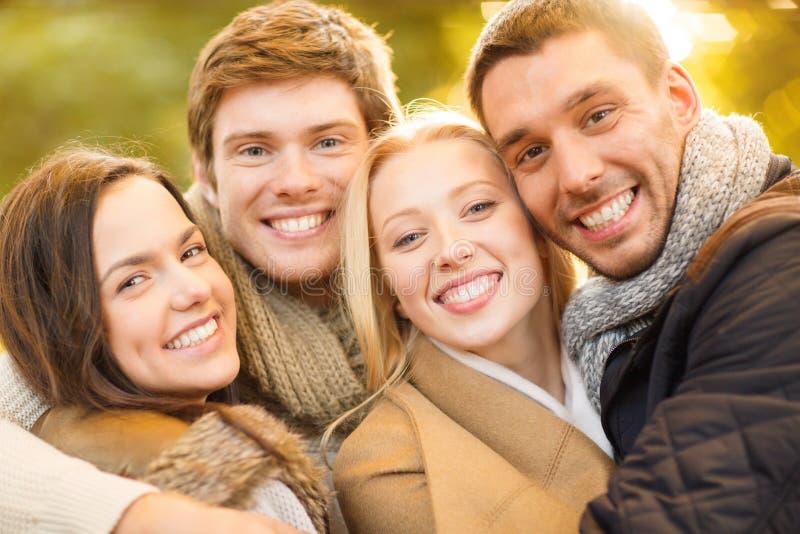 Gruppo di amici divertendosi nel parco di autunno fotografia stock libera da diritti