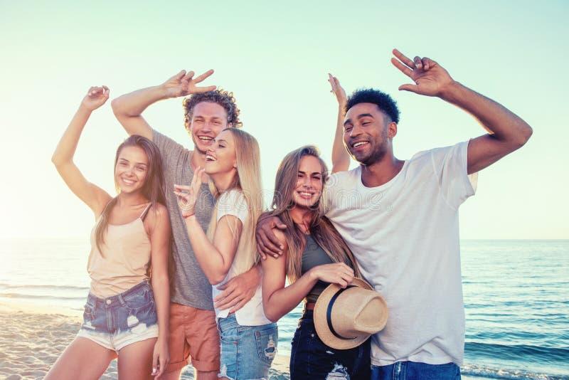Gruppo di amici divertendosi sulla spiaggia Concetto di estate immagini stock
