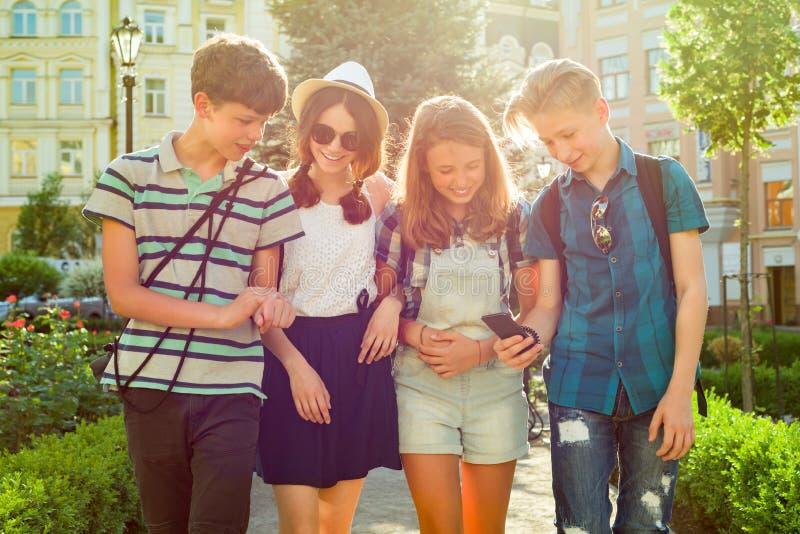 Gruppo di amici felici 13, 14 anni degli adolescenti camminante lungo la via della città immagini stock