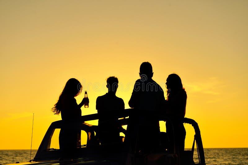 Gruppo di amici felici che fanno partito in giovani automobilistici divertendosi champagne bevente immagine stock
