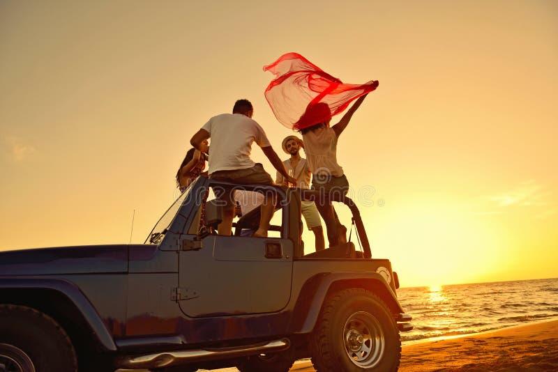 Gruppo di amici felici che fanno partito in giovani automobilistici divertendosi champagne bevente fotografia stock libera da diritti