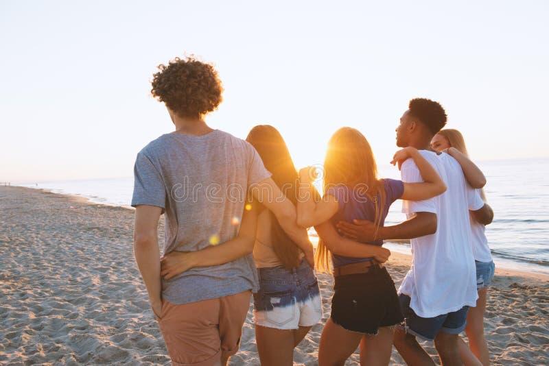 Gruppo di amici felici divertendosi alla spiaggia dell'oceano fotografia stock