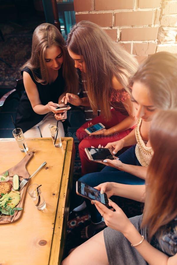 Gruppo di amici femminili abbastanza giovani che mangiano insieme in caffè facendo uso degli smartphones fotografia stock