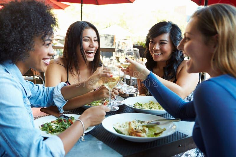 Gruppo di amici femminili che godono del pasto al ristorante all'aperto fotografia stock