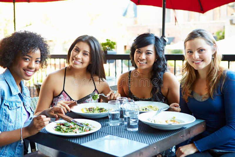 Gruppo di amici femminili che godono del pasto al ristorante all'aperto immagine stock