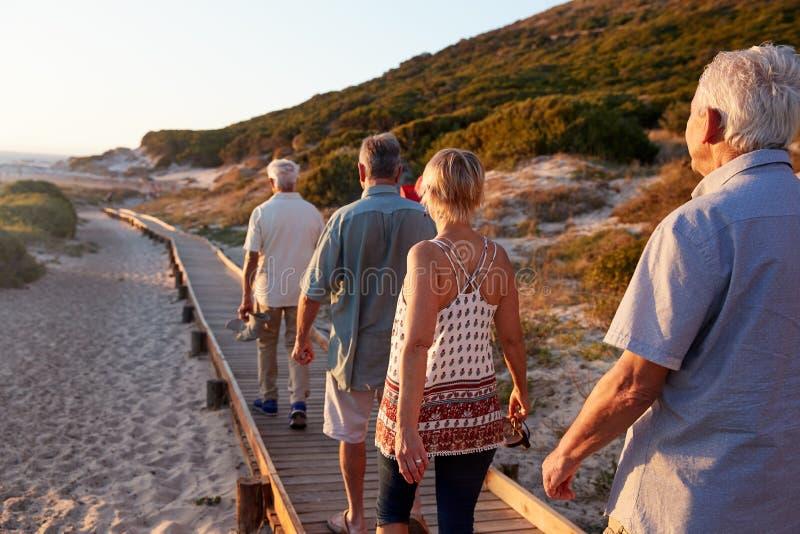 Gruppo di amici senior che camminano lungo il sentiero costiero alla spiaggia sulla vacanza del gruppo di estate fotografia stock